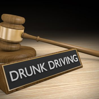 DUI law concept of a wooden court gavel lying next to a sign that reads Drunk Driving.