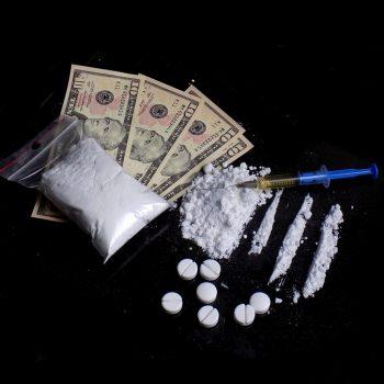 Injection syringe on cocaine drug powder lines and pile, pills, cocaine powder bag and dollar money bills on black background
