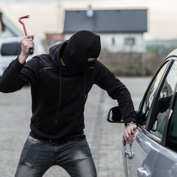 Man dressed in black with a balaclava on his head breaking a glass in car with crowbar. Car thief car theft concept