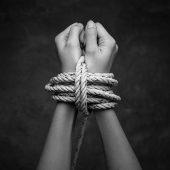 Hands of a missing kidnapped abused hostage victim woman tied up with rope in emotional stress and pain afraid restricted trapped call for help struggle terrified locked in a cage cell.